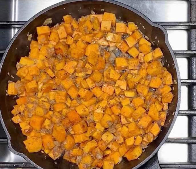 Cast Iron Skillet with Cooked Sweet Potatoes, Diced White Onion,Garlic, and Cinnamon   Kale Sweet Potato Hash   The Radiant Root