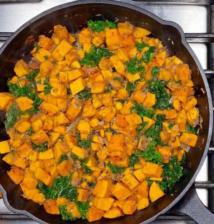 Cast Iron Skillet with Cooked Sweet Potatoes, Diced White Onion,Garlic, Cinnamon, and Kale   Kale Sweet Potato Hash   The Radiant Root