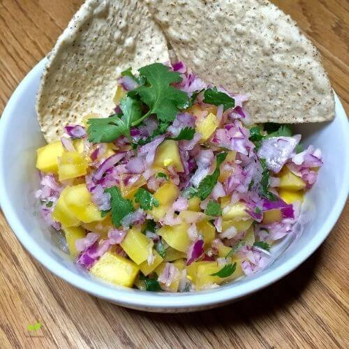 Mango Salsa in a white bowl with gluten-free tortilla chips | The Radiant Root