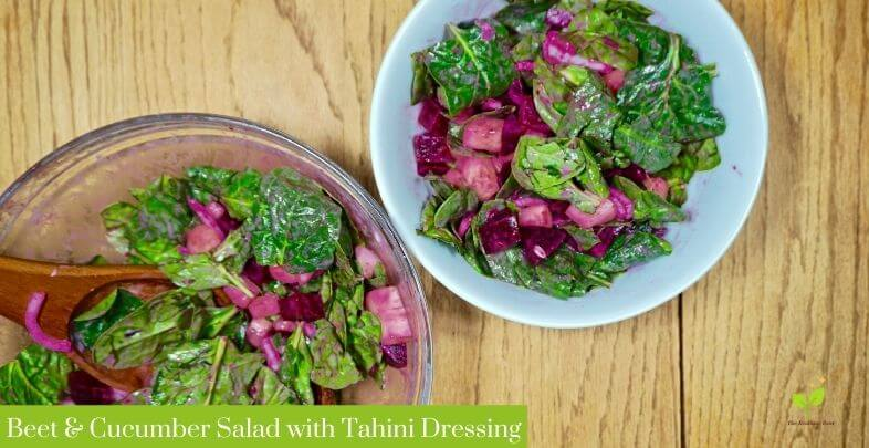 Beetroot and cucumber salad with tahini dressing in a white bowl on a wooden table | The Radiant Root